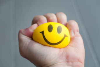 Hand squeezing yellow stress ball with smiley face